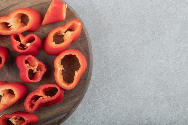 Segmenten van zoete rode paprika's op een houten bord.