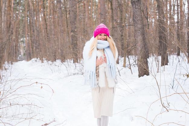 Seizoen en mensen concept aantrekkelijke blonde vrouw gekleed in witte jas en roze hoed staan