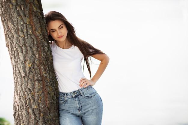 Seizoen en mensenconcept - mooie gelukkige jonge vrouw. aantrekkelijk glimlachend jong meisje die jeanskleren dragen die tijd in openlucht doorbrengen bij het park, die op een boom leunen. horizontaal