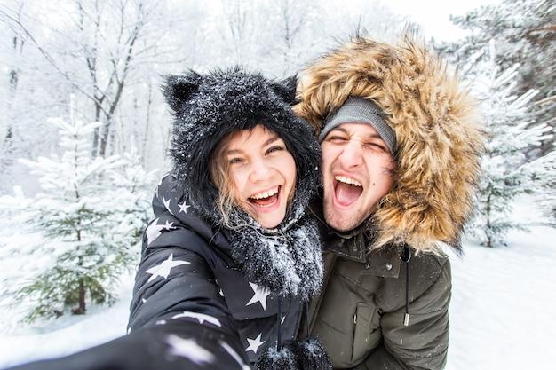 Seizoen, liefde, technologie en recreatie concept - gelukkige paar selfie te nemen door smartphone tijdens de winter