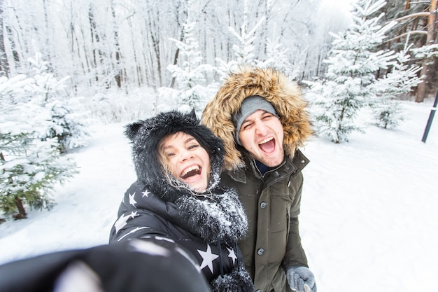 Seizoen liefde technologie en vrije tijd concept gelukkige paar selfie nemen door smartphone in de winter