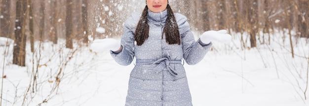 Seizoen, vrije tijd en mensen concept - close-up van de vrouw is blij en gooit sneeuw in de winterse natuur