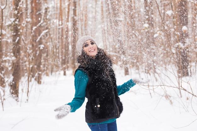 Seizoen, vrije tijd en mensenconcept - jonge vrouw is gelukkig en gooit sneeuw in de winteraard