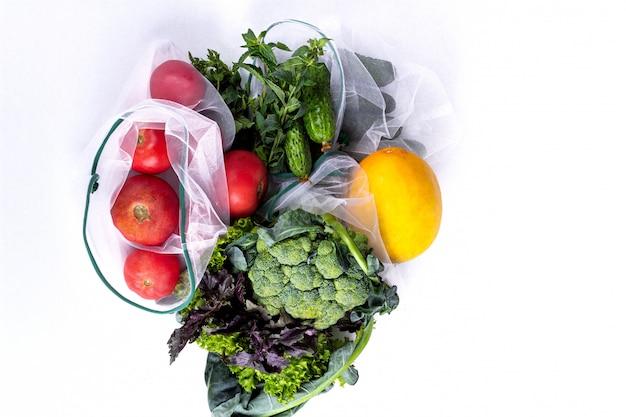 Seizoensfruit en groenten op wit. rauw biologisch vers voedsel van de markt. winkelen zonder afval. herbruikbare boodschappentassen