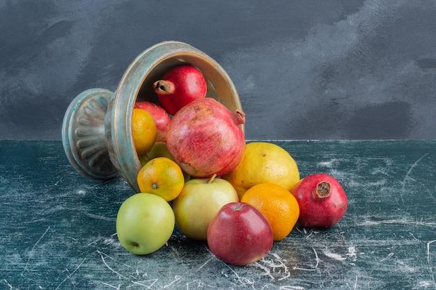 Seizoensfruit in een schotel op blauwe ondergrond.