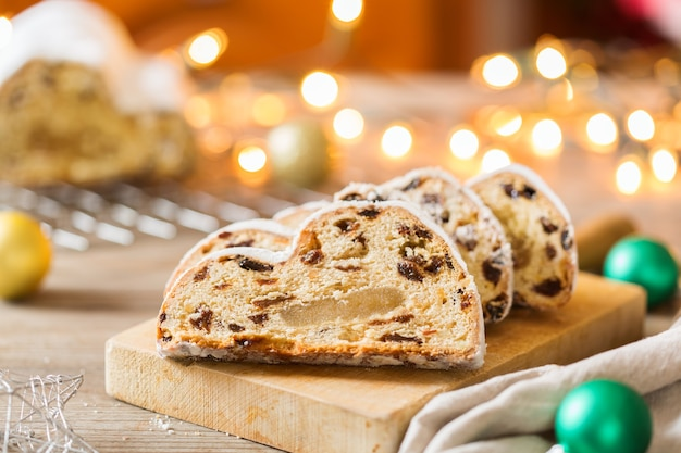 Seizoensgebonden eten en drinken, winterconcept. traditionele europese duitse zelfgemaakte kerstcake, gebakdessert stollen op een houten ondergrond met feestelijke decoratie.