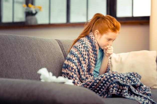 Seizoensgebonden koude. ongelukkig roodharig meisje hoest in haar hand terwijl ze verkouden is