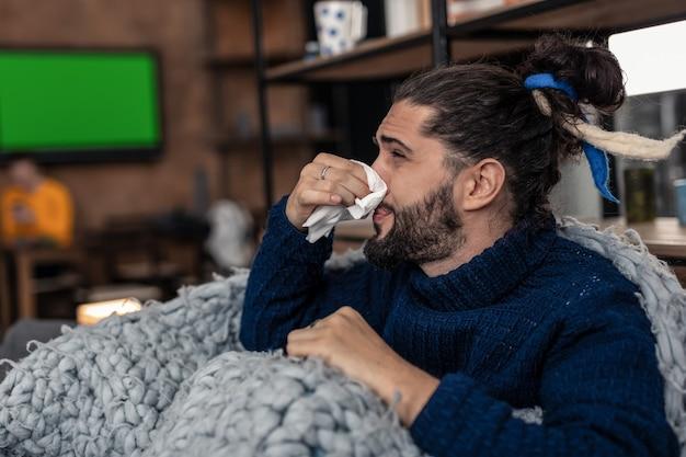 Seizoensgebonden koude. trieste aangename jonge man die zijn neus vasthoudt terwijl hij verkouden is