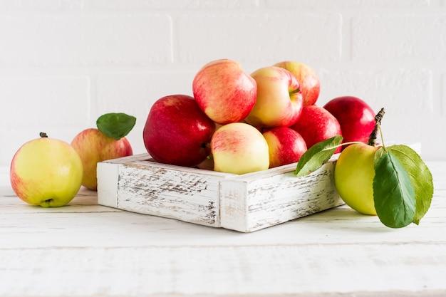 Seizoensgebonden rode, gele appels in een decoratieve doos tegen de achtergrond van een witte bakstenen muur.