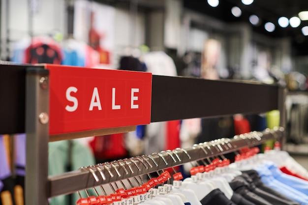 Seizoensgebonden verkoop, vakantiekortingen in winkelcentrum, black friday. de verkooptijd van het nieuwe jaar bij europees winkelcentrum. kerstpromoties in kledingwinkel. sportkleding en kleding hangen aan hangers.