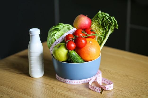 Seizoensgroenten en fruit in een kom met meetlint en fles