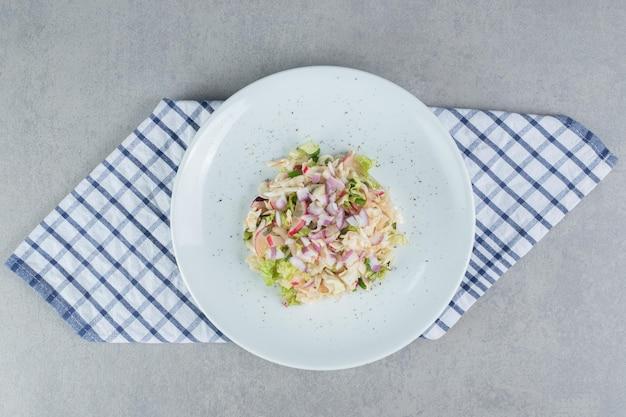 Seizoenssalade met gemengde ingrediënten met groenten en fruit in een witte schotel.