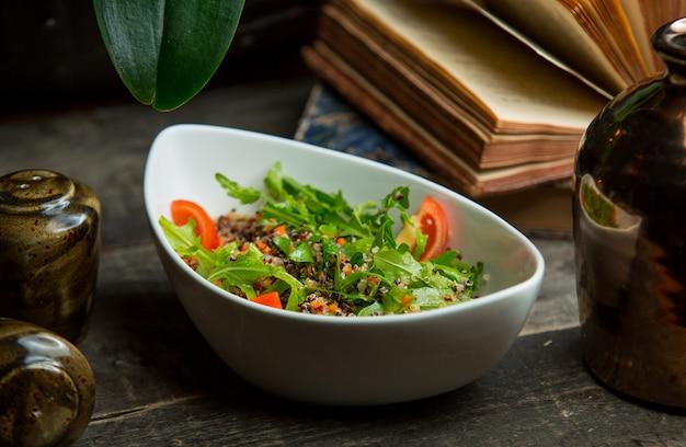Seizoenssalade met rokabladeren en plakjes tomaat
