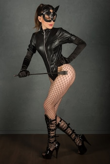 Seksspelletjes voor volwassenen. mooie dominante brunette vamp meesteres meisje in latex lichaam, handschoenen en bdsm zwart lederen fetish kat masker poseren met rijzweep. - afbeelding