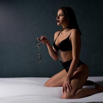 Seksueel bdsm-speeltje. outfit voor het spelen van bdsm-spelletjes. schoonheid dame met handboeien. perfecte sexy kont