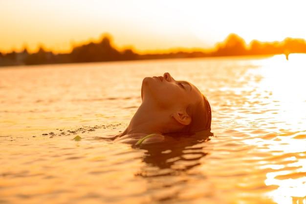 Seksuele jongedame in de zee bij warme zonsondergang