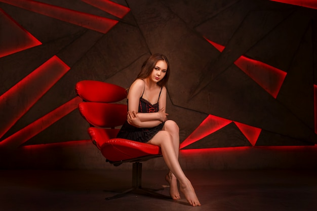 Seksuele meid met donkere haren, zittend op een rode fauteuil