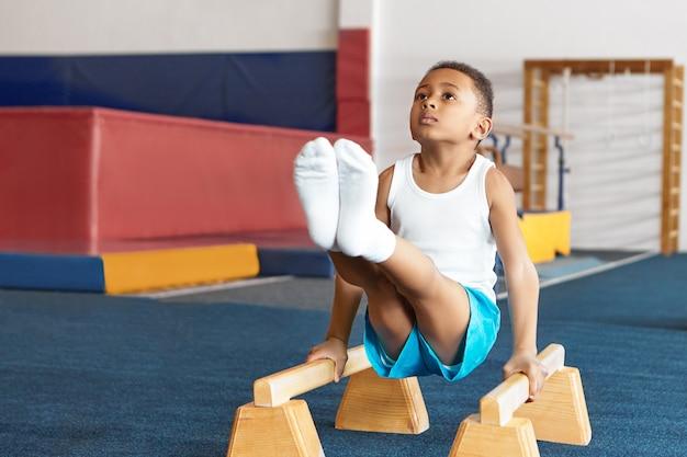 Seld vastberaden gedisciplineerde afro-amerikaanse kleine sportman in wit t-shirt