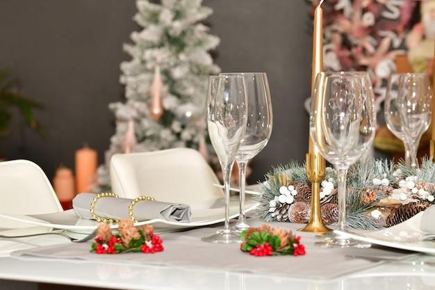 Selecteer de focus van een tafel met glazen, een krans met dennenappels en andere kerstversieringen