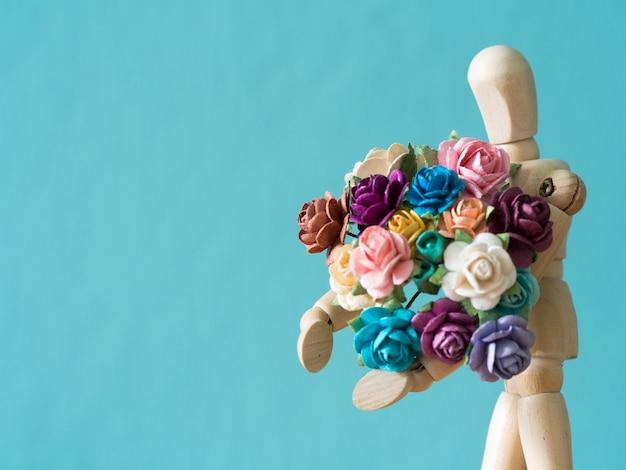 Selecteer focus van houten pop. de houten pop houdt bloem en staande op de houten tafel.