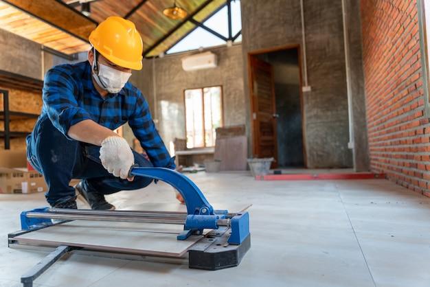 Selecteer focus vloertegel snijapparatuur, aziatische ambachtelijke tegelzetter op bouwplaats, werknemer snijdt een grote plaat tegel tijdens de bouw van een huis