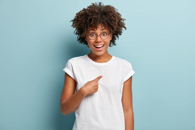 Selecteer mij alstublieft. vrolijke vrouw met donkere huid wijst met de vinger naar zichzelf, kan haar geluk niet geloven, draagt een casual t-shirt, geïsoleerd over een blauwe muur, zegt dat ik ben wat je nodig hebt.