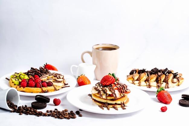 Selectie fruitpannenkoekjes gegarneerd met warme chocolademelk