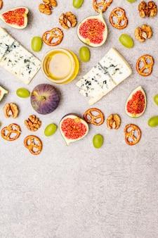 Selectie kaasvoorgerecht of wijnsnackset. blauwe kaas, vijgen, honing, walnoten, pretzels