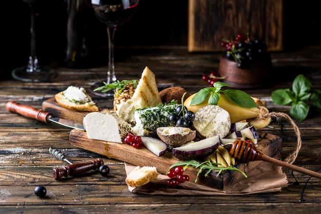 Selectie kaasvoorgerecht. rode bessen, honing, basilicum, druiven en noten op rustieke houten bord