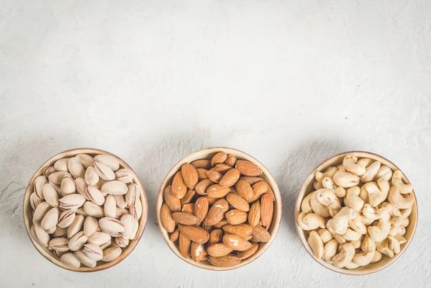 Selectie noten op een witte stenen tafel, in een kom en verspreid: amandel, cashewnoten en pistache. bovenaanzicht