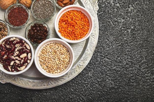 Selectie van bonen en noten in kommen: quinoa, chia, linzen, bonen, amandelen, walnoten, koffiebonen op donkere betonnen achtergrond