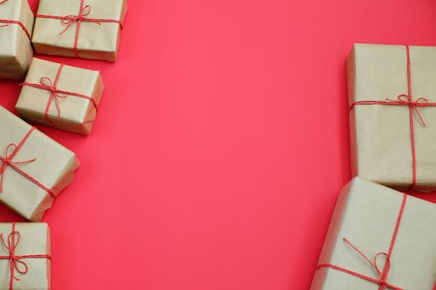 Selectie van cadeautjes in handgeschept papier verpakking en rode bindgaren bogen achtergrond
