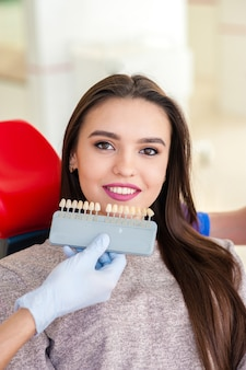 Selectie van de kleur van tanden voor een mooi meisje in de tandheelkunde.