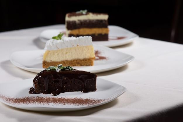 Selectie van desserts in een restaurant met een diagonale lijn van drie verschillende soorten cake geserveerd op borden met een plakje of chocoladetaart op de voorgrond