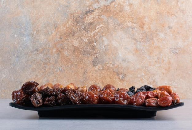 Selectie van droge vruchten op een schotel op betonnen ondergrond.