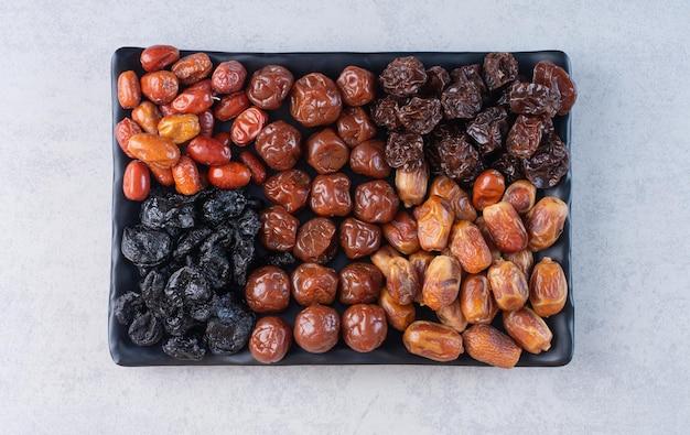 Selectie van droog fruit op een schotel op betonnen ondergrond.