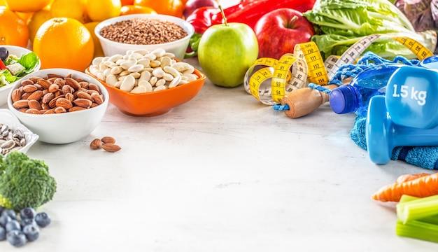 Selectie van gezond voedsel groenten fruit amandelen salade oefeningshulpmiddelen en meetlint