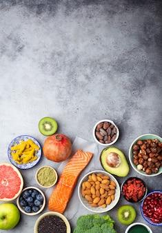 Selectie van gezonde producten en superfoods: zalm, fruit, groenten, bessen, goji, spirulina, matcha, quinoa, chia, noten met kopieerruimte. schoon eten concept, grijze achtergrond, bovenaanzicht, close-up