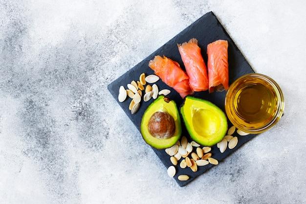 Selectie van gezonde vetbronnen, avocado, zalm, noten, olijfolie op een zwarte plaat. het concept van gezond eten. bovenaanzicht, kopie ruimte, grijze achtergrond