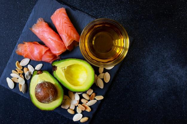 Selectie van gezonde vetbronnen, avocado, zalm, noten, olijfolie op een zwarte plaat. het concept van gezond eten. bovenaanzicht, kopie ruimte, zwarte achtergrond