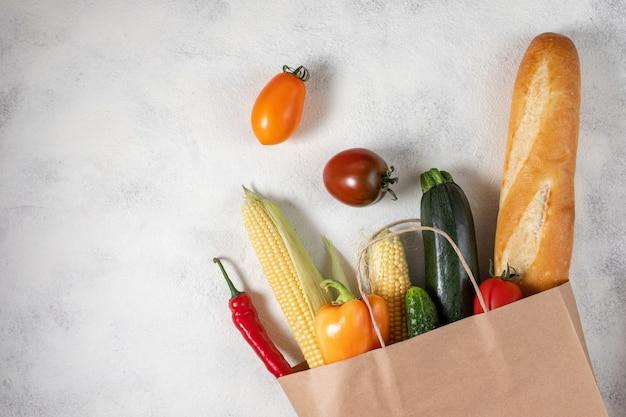 Selectie van gezonde voeding. boodschappentas papier vol met verse groenten. plat eten op tafel.