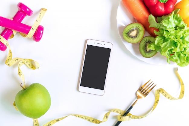 Selectie van gezonde voeding met fruit, groenten, halter, meetlint en smartphone. oefening voor een goed gezondheidsconcept. biologisch voedsel, dieet concept. bovenaanzicht, kopieer ruimte.