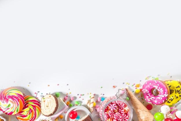 Selectie van kleurrijke snoepjes. set van verschillende snoepjes, chocolaatjes, donuts, koekjes, lolly's, ijs bovenaanzicht op witte achtergrond