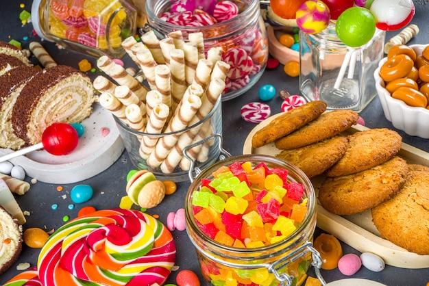 Selectie van kleurrijke snoepjes. set van verschillende snoepjes, chocolaatjes, donuts, koekjes, lolly's, ijs bovenaanzicht op zwarte betonnen achtergrond