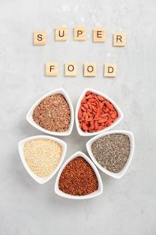 Selectie van super voedsel in witte kommen op grijze concrete achtergrond.