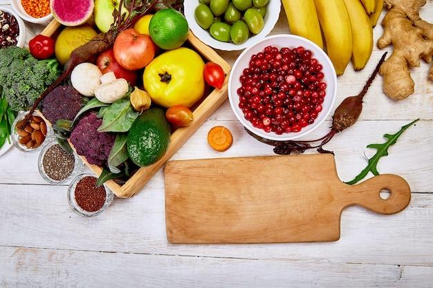 Selectie van superfoods rond snijplank op witte achtergrond.