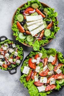 Selectie van traditionele griekse salade in kommen. witte achtergrond. bovenaanzicht.