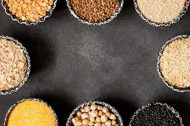 Selectie van verschillende kleurrijke granen met kopie ruimte op het zwarte oppervlak