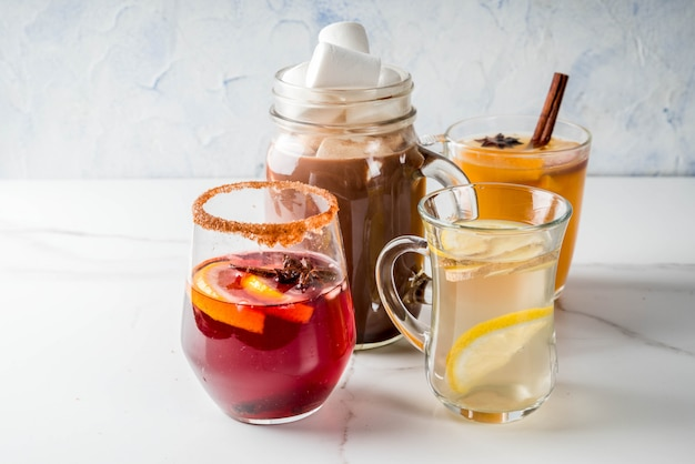 Selectie van verschillende traditionele herfstdranken: warme chocolademelk met marshmallow, thee met citroen en gember, kruidige sangria met witte pompoen, glühwein. op witte marmeren tafel, kopie ruimte, selectieve aandacht