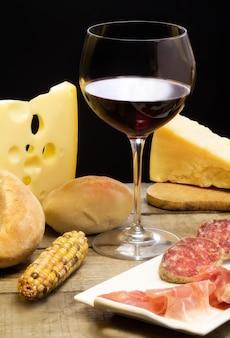 Selectie van zuivelproducten, salami, parmaham en rode wijn